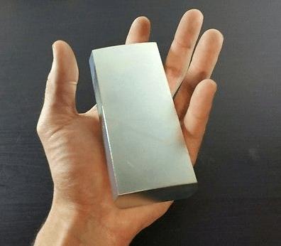 Silný voľne dostupný neodymový magnet v ruke človeka